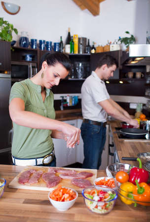 Young couple working in kitchen photo