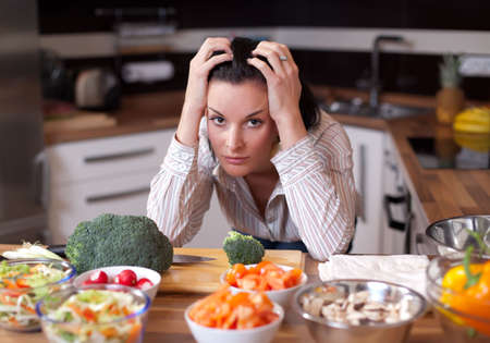 Depressed and sad young woman in kitchen Stock Photo