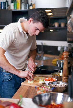 Young handsome man preparing lunch in kitchen photo