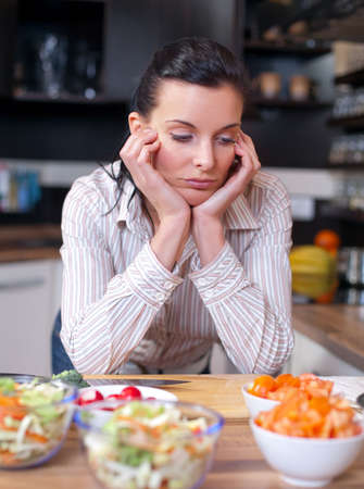 Depressed and sad woman in the kitchen photo