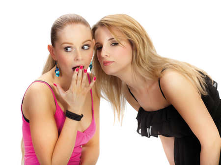 slander: Two young woman wispering secrets - isolated Stock Photo