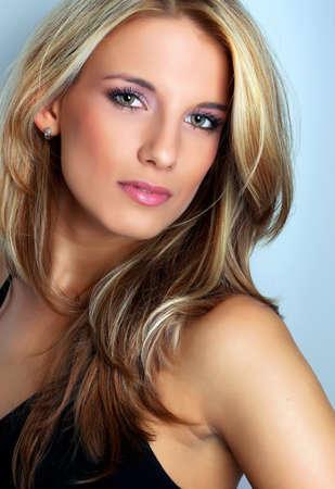cabello rubio: Retrato de mujer joven y guapa - disparo de estudio sobre fondo azul