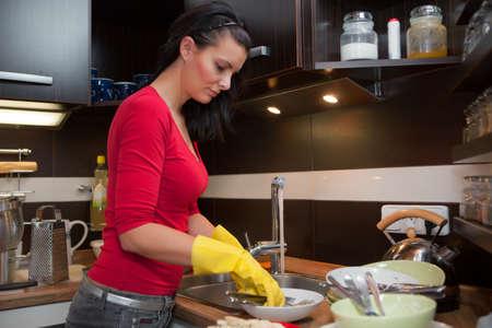 lavar trastes: Joven mujer hermosa hacer la limpieza en la cocina Foto de archivo