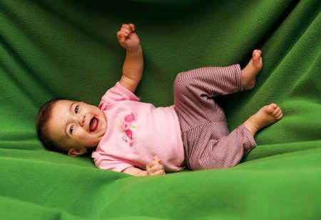 Happy smiling child on green blanket  Stock Photo - 12684404
