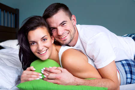 Portrait of happy young couple in bed Stock Photo