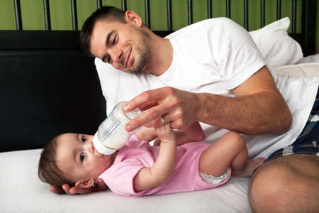 Portrait of father feeding daughter at home