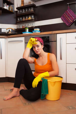 Portrait of attractive overworked  woman in kitchen Фото со стока