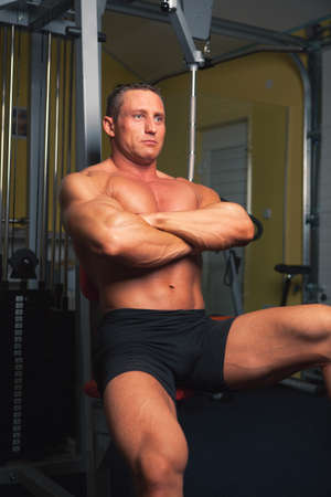Bodybuilder sits in his training room  Stock Photo - 14435228