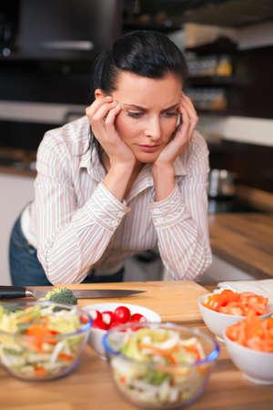 agotado: Mujer joven deprimido y triste en la cocina