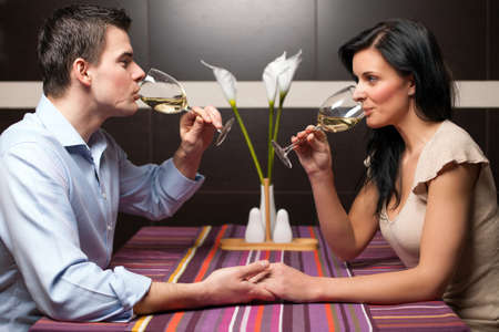 Attractive young couple drinking wine and flirting  版權商用圖片