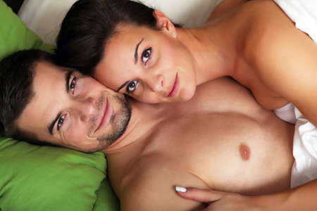 Portrait of young romantic couple in a bed  photo