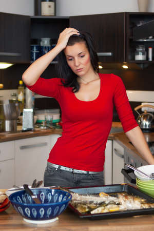Beautiful unhappy woman standing in kitchen  photo