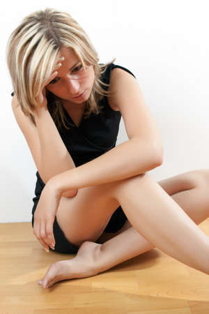 depressed teenager: Young attractive woman sitting on floor - depressed and sad