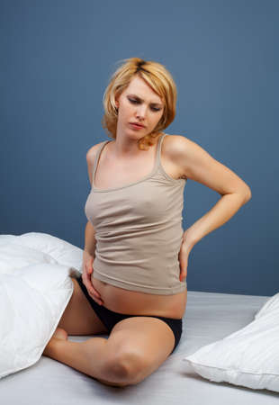 Tired pregnant woman sitting on bed - studio shot photo
