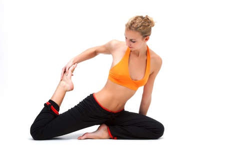 Younge woman stretching the muscles of her legs - white background photo