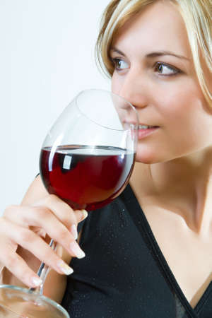 Young woman drinking red wine - white background 版權商用圖片