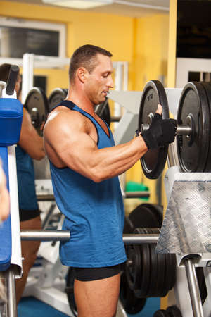Strong man preparing his training machine in fitness club photo