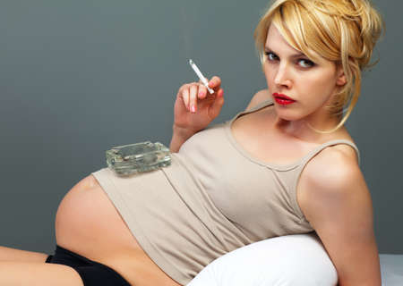Pretty pregnant with a cigarette and ashtray photo