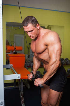 Handsome bodybuilder excercise in fitness club photo