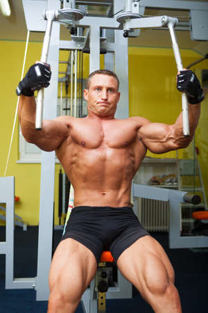 Muscle shaped man exercise on sport gym in fitness club  photo