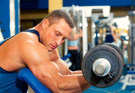 muscular body: Man with weight training equipment on sport gym club