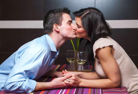 Young couple siiting in restaurant and kissing photo