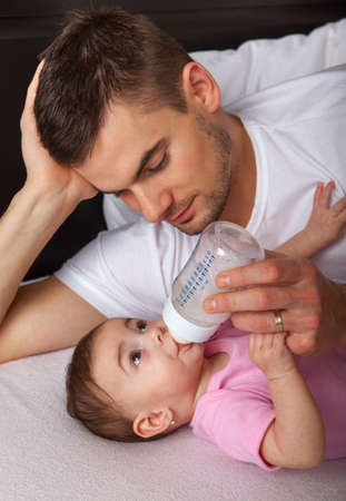 Portrait of father feeding daughter at home  photo