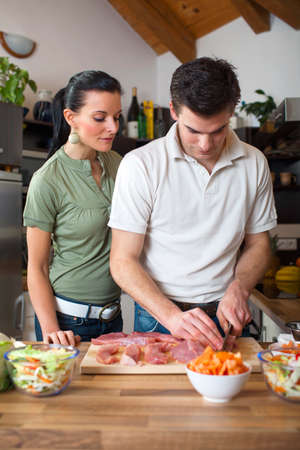Young happy couple preparing lunch in kitchen  photo