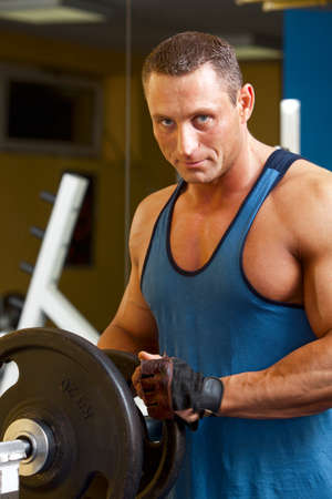 young add: Strong man preparing his training machine in fitness club