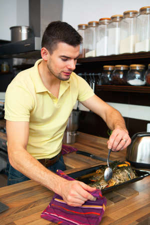 Young handsome man preparing fish in kitchen  photo