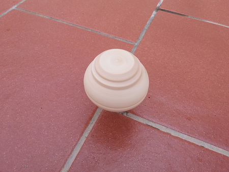 Wooden spinning top while spinning on the ground