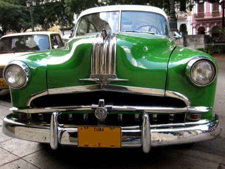 american revolution: Front view of a green old car in the street of Havana Cuba