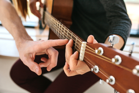 Learning to play the guitar. Music education. Standard-Bild