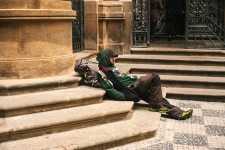 Prague, Czech Republic December 24, 2016 - Homeless hungry poor man sitting on the sidewalk in the city center. Unhappy man. Prague