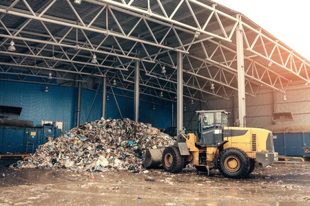 délivrance: The bulldozer will clean the waste dump. Waste processing plant. Technological process. Business for sorting and processing of waste. Banque d'images
