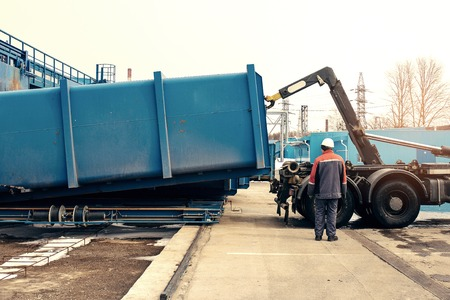 Loading container with waste to a special machine for subsequent transportation to a waste disposal plant. Waste processing plant. Business for sorting and processing of waste.