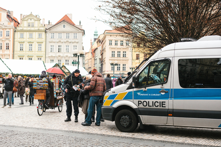 Prague, Czech Republic - December 25, 2016: Czech policemen on a Christmas day help the tourist - show the desired place of attractions on the map. Respectful attitude to tourists from the authorities