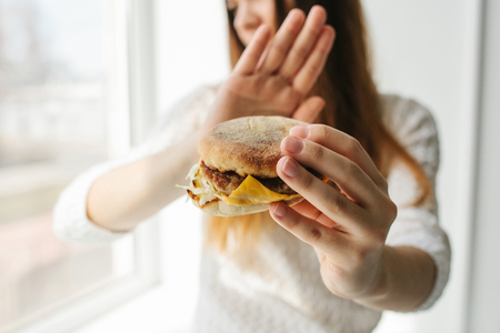 A young girl shows a sign by hand signifying there is no burger. Conceptual image of refusal from unhealthy eating. Stock Photo