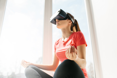A young beautiful woman in virtual reality glasses makes aerobics remotely. Future technology concept. Classes in single sports remotely. Selective focus on the fingers of the hand.