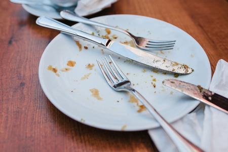 feast: Dirty plate. Empty plate after eating place on wooden table in coffee shop.