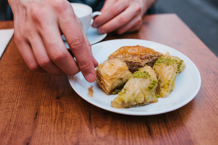 A man in a cafe eats coffee with a traditional oriental baklava dessert. Eastern food. Turkish dessert. Food.