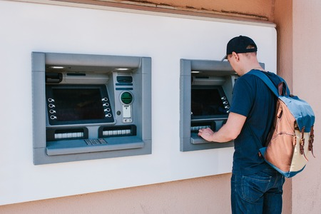 De toerist trekt geld terug van de geldautomaat voor verdere reis. Financiering, creditcard, onttrekking van geld. Levensstijl. Reis. Vakantie. Stockfoto