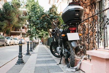 The motorcycle is parked on the street and closed to a special lock against theft. Safety and prevention of crime.