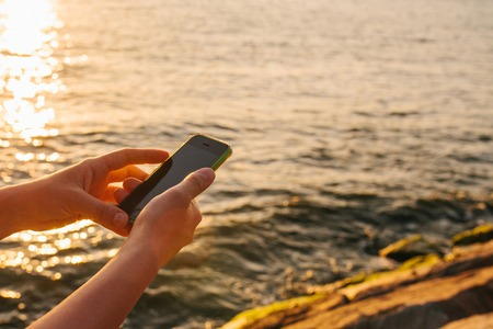 Female hands hold the phone. Use the phone to connect in travel. Travel concept. View of the sea and sunset in the background.