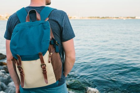 A tourist with a backpack on the coast. Travel, tourism, recreation. Stock Photo