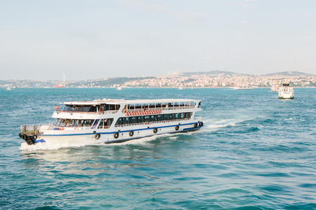 The ship sails along the blue water of the Bosphorus against the backdrop of a beautiful view of the European part of Istanbul. Scenic panoramic view. Travel, rest, vacation.