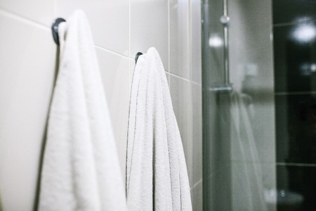 White towels hang on the wall in the bathroom. Cleanliness, shower.