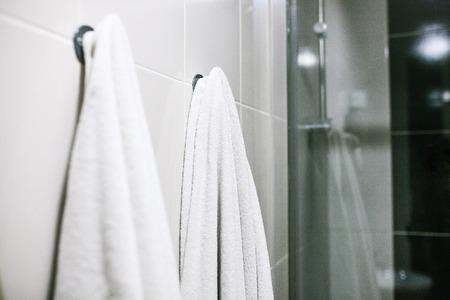 白いタオルは、バスルームの壁にしがみつきます。清潔、シャワー。