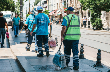 groundskeeper: Istanbul, June 15, 2017: Three street janitors in uniforms are walking down the street holding brooms and dust pans. Editorial