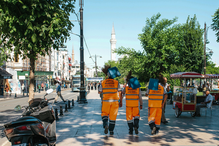 groundskeeper: Istanbul, June 15, 2017: Three street janitors in bright orange uniforms are walking down the street holding brooms and dust pans.